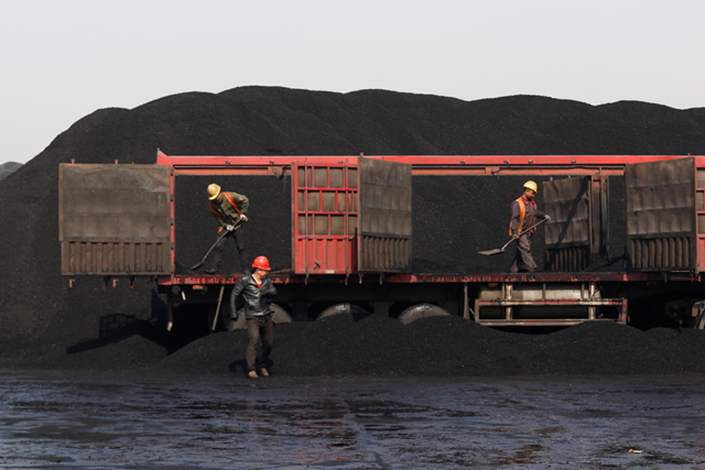 Workers move coal to a transport vehicle in Tianjin on Wednesday. Tianjin has banned polluting diesel-powered coal trucks from its port three months ahead of schedule. Photo: Xia Weicong/Caixin