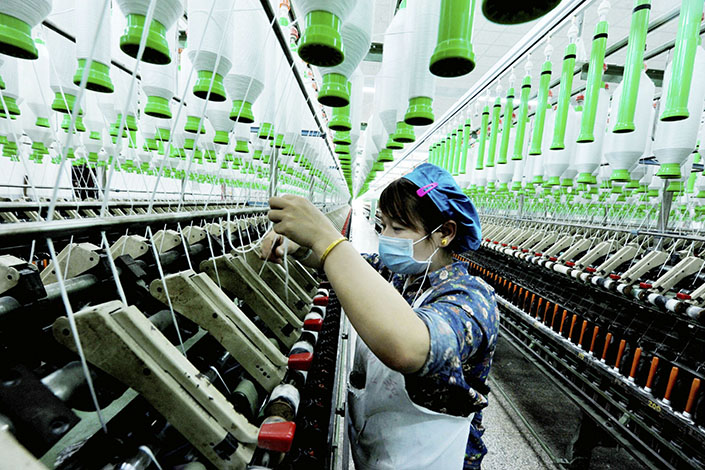 China's gross domestic product growth accelerated year-on-year for the second straight quarter in the January-through-March period. Above, a Chinese worker handles production of yarn at a textile factory in Yushan county, Jiangxi province, on March 28. Photo: IC