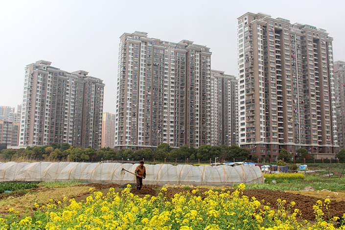 The Ministry of Land and Resources said Monday that average residential land price in China increased 7.91% in 2016, up nearly 4 percentage points from a year earlier. Above, a farmer works near residential real estate in Changzhou, Jiangsu province, on March 25. Photo: Visual China