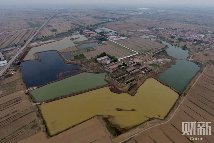 Six ponds next to a high-speed rail line running through the Tongjiazhuang village in Jinghai district, Tianjin. The six ponds are connected by dikes and cover an area of 150,000 square meters. Photo: Chen Weixi/Caixin