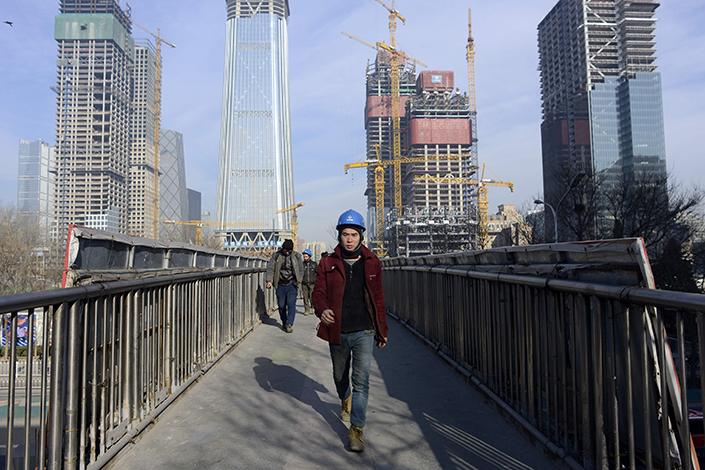 A workman crosses a bridge in Beijing on Dec. 16, 2016. Property investment in the Chinese capital is falling as government curbs on home purchases take effect. Photo: Visual China
