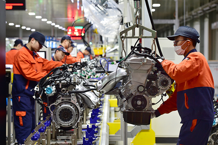 Chinese regulators will strictly limit construction of new car manufacturing plants in a bid to rein in a runaway buildup. Above, workers assemble engines in a car production line of Zhejiang Geely Holding Group in Yiwu, Zhejiang province, on Feb. 7. Photo: Visual China