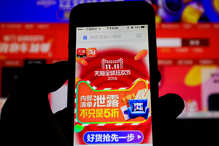 A customer browses Alibaba's Tmall Global website on a smartphone. The e-commerce giant is looking to expand into Hong Kong, Taiwan, Singapore and Malaysia. Photo: Visual China