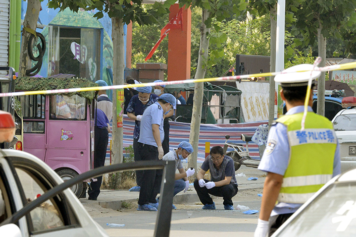 Police say they have identified a 22-year-old man as the suspect in a deadly explosion Thursday near a kindergarten (preschool) in Fengxian county in east China's Jiangsu province that killed eight people and injured at least 65. Above, police officers examine the entrance to the kindergarten on Friday. Photo: Fan Xi/Caixin
