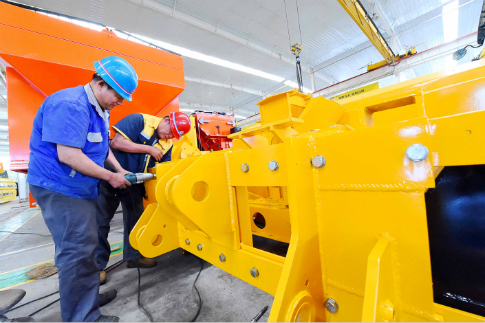 The official manufacturing Purchasing Managers Index (PMI) edged down to 51.4 in July from 51.7 in the previous month, the first decline since April. Above, workers assemble a snowplow on Thursday at a factory in Weifang, Shandong province. Photo: Visual China