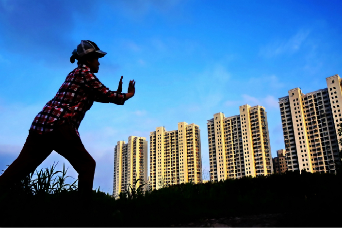Beijing plans to roll out a program similar to Shanghai's in which qualified homebuyers pay only part of the purchase price of an apartment, with the municipal government paying the rest. The homebuyer will then have the option to pay the rest later. Above, a woman exercises in front of a building in Shanghai in June 2012. Photo: Visual China