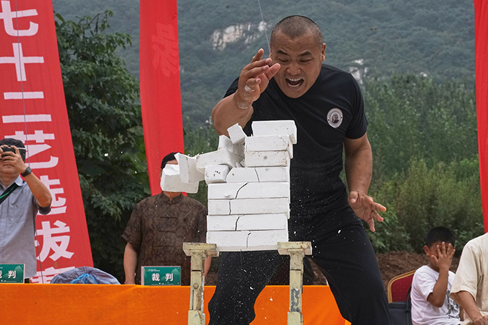 """Zhang Longxiang breaks eight bricks with his hand on July 30 during a competition organized by the Shaolin Temple in Henan province. Zhang won the title of """"Iron Hand champion."""" Photo: Liang Feiying/Caixin"""