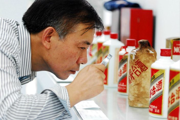 Kweichow Moutai Co. Ltd. has announced plans to put its various financial businesses into one holding unit. Above, a prospective buyer carefully examines a bottle of Maotai at an auction in Jiangxi province in September 2011. Photo: Visual China