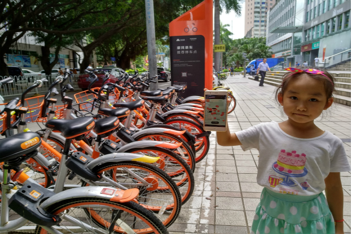 Mobike users in major cities across China say they were unable to unlock the company's trademark orange and silver two-wheelers at about 9 a.m. on Thursday. Above, a girl shows the Mobike app on a smartphone this month in Shenzhen. Photo: Visual China