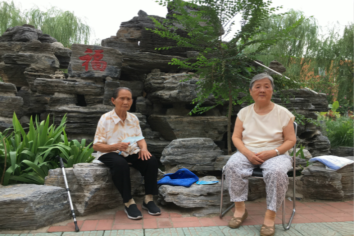 Two women sit in front of an artificial mountain at the Laowulao Elder Care Facility in Beijing's Fengtai district in July. Photo: Cecilia Chang/Caixin