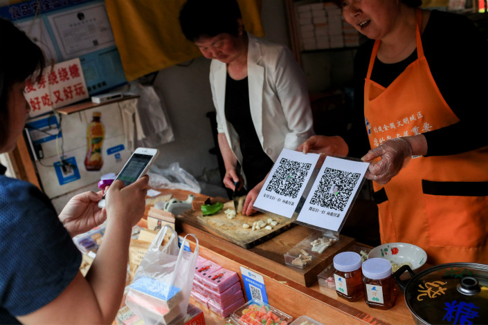 Tencent's new service will allow users to earn interest from their WeChat balances. Above, a customer uses her smartphone on May 15 to pay at a store in Shanghai that accepts payment via WeChat and rival Alipay. Photo: Visual China