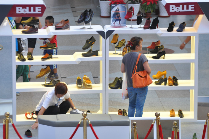 Belle International Holdings Ltd. is the world's largest maker of women's shoes, but its business has been hurt by a perception that its fashions aren't up-to-date and by online competition. Above, Belle autumn shoes are displayed in Shenyang, Liaoning province, in September 2014. Photo: Visual China