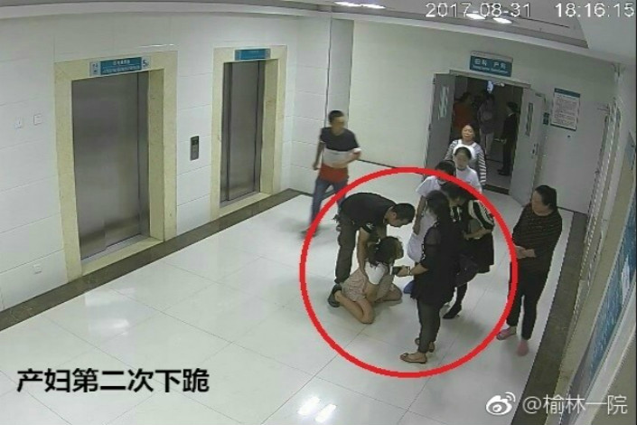 A video screen grab from the First Hospital of Yulin in Shaanxi province shows 26-year-old Ma Rongrong kneeling in front of her family in a hospital hallway on Aug. 31. The video has no sound so it is unknown whether she was kneeling in pain or begging the family for permission to let her have a cesarean section. Ma later committed suicide by jumping out of a fifth-floor window at the hospital.Photo: First Hospital of Yulin