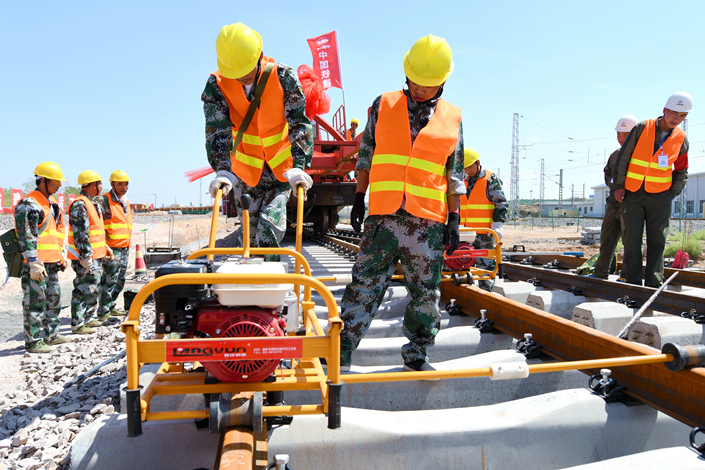 China's railway regulator fined China Railway Construction Co. Ltd. (CRCC) and China Railway Group Ltd. after finding that respective branches of the two companies had subcontracted projects illegally. Above, CRCC workers set tracks for a high-speed rail line in Wuzhong, Ningxia Hui autonomous region, on Sept. 2. Photo: Visual China