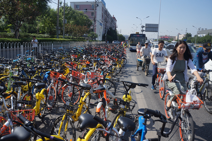 Commuters cycle past shared bicycles parking along the street in Beijing on Aug. 2. Several cities have asked bike-sharing companies to stop putting additional bikes onto city roads. Photo: Visual China.