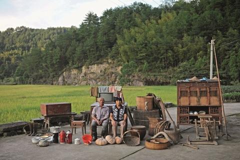 在浙江丽水青田万阜乡,74岁的董碎楷和66岁的蒋真妹坐在自家家当中合影。家当有旧式的木箱子、电视机、木桶、橱柜、簸箕……应有尽有。