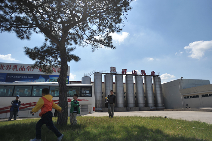 China Huishan Dairy is facing a demand from HSBC Holdings PLC that Huishan immediately repay a $200 million loan that it has defaulted on. Above, children play in front of the Huishan plant in Shenyang, Liaoning province, in May 2014. Photo: IC