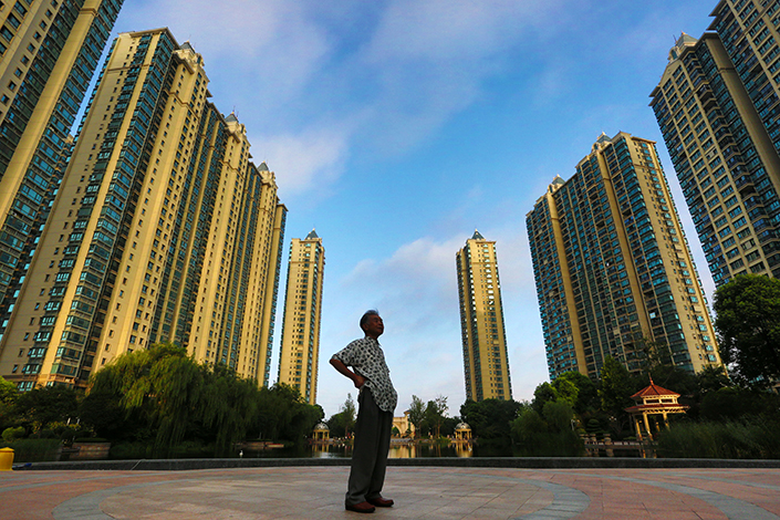 Several companies that manage rental apartments are working with regulators over the issuance of securities, particularly real estate investment trusts, backed by home rental properties. Above, high-rise residential buildings tower above a passer-by on Sept. 1 in Jiangsu province. Photo: Visual China