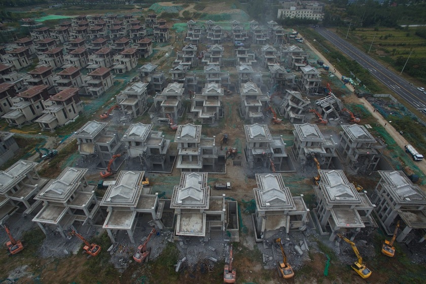 Some 60 excavators knock down rows of villas built by Xi'an HNA Property in Xi'an, capital of northwestern China's Shaanxi province on Thursday. The Caotang Shanju development was reportedly built on a piece of land approved for tourism use, that was then illegally used for residential purposes. This action is part of Xi'an's recent campaign to crack down on illegally built properties. Photo: VCG_Gallery: Xi'an's War on 'Illegal' Villas Thunders On