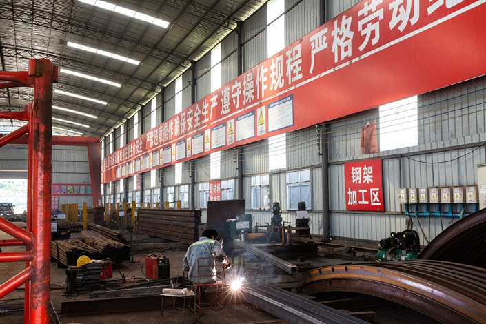 A steelworker works in a warehouse near the Luang Prabang railway bridge in Laos, one part of the China-Laos Railway being built by China Railway Group Ltd., on Oct. 21, 2018. Photo: VCG