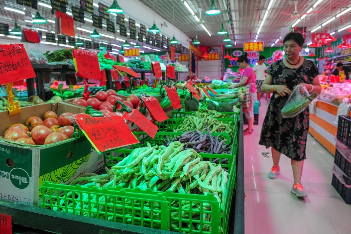 People browse goods at a supermarket in Shenyang, Liaoning province, on Aug. 9, 2019. Photo: VCG