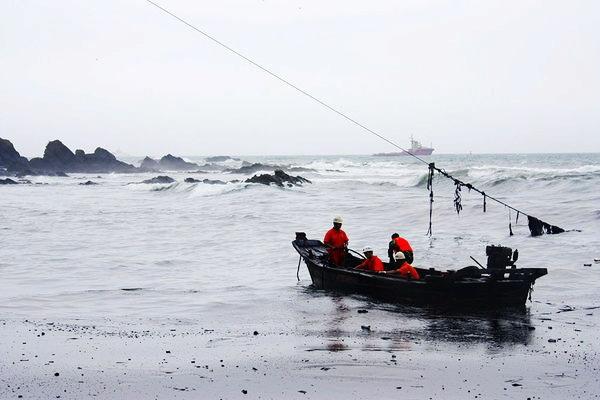 7月20日,消防战士在海面上清理油污。 东方IC _大连油管爆炸事故一名战士清理油污时牺牲