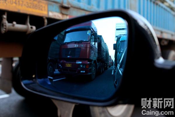 8月26日,绵延三四十公里的运货大卡车堵在京藏高速公路河北怀安段,距北京还有大约250公里。大部分卡车已经在此堵了两天,没有人告诉他们什么时候才能放行。 财新记者 牛光 摄 _京藏行路难