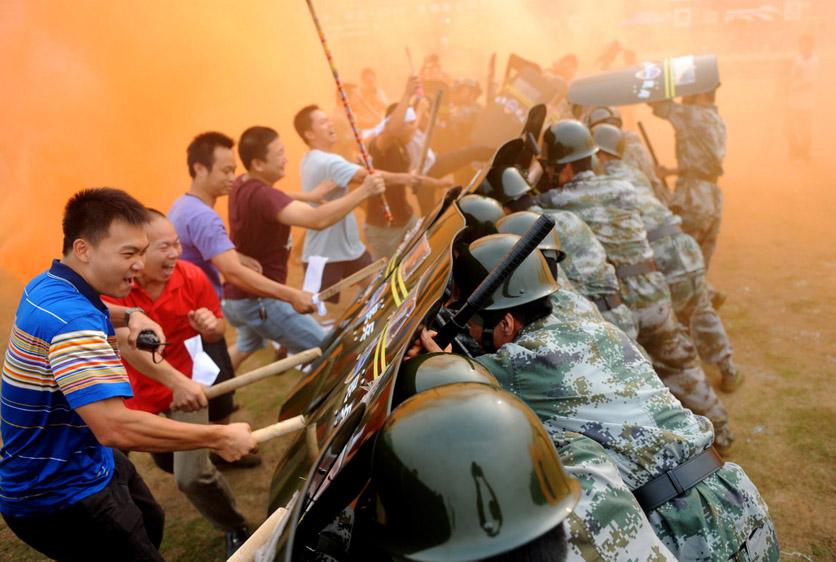 9月28日,为遂行亚运安保任务,广东佛山市举行佛联-2010演练。这是近年来佛山市举行的最大规模军地联合实兵演习。图为在处置群体性突发事件演习中,民兵使用盾牌进行防御。 CFP _财新每周图片(2010.9.25-10.1)