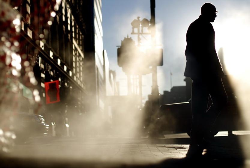 10月13日,在美国费城,一名男子走在街上,沐浴阳光。 人民图片/Fotomore.cn  _财新每周图片(2010.10.9-10.15)