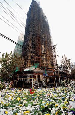 """11月19日,上海""""11·15""""特大火灾事故现场,市民自发敬献的花束已将整个胶州路728号大楼四周铺满。"""