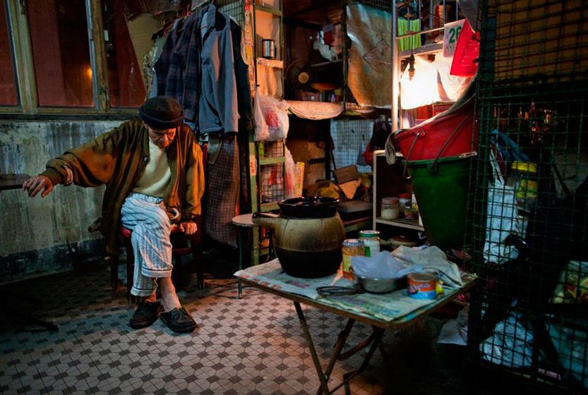 11月27日,香港,78岁老人梁书(音译)坐在他的笼屋床位旁边。笼屋又称床位寓所,是指一个单位内有十二伙或以上租户,并共享厨房、厕所。 CFP _房价飙升 香港笼屋居民难觅栖身之所