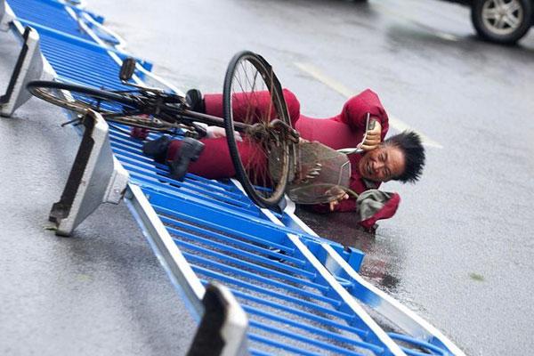 8月7日,台风梅花袭击江苏启东,骑行的市民被狂风吹倒。 陈中秋/东方IC  _梅花袭击江苏启东 市民风雨中寸步难行