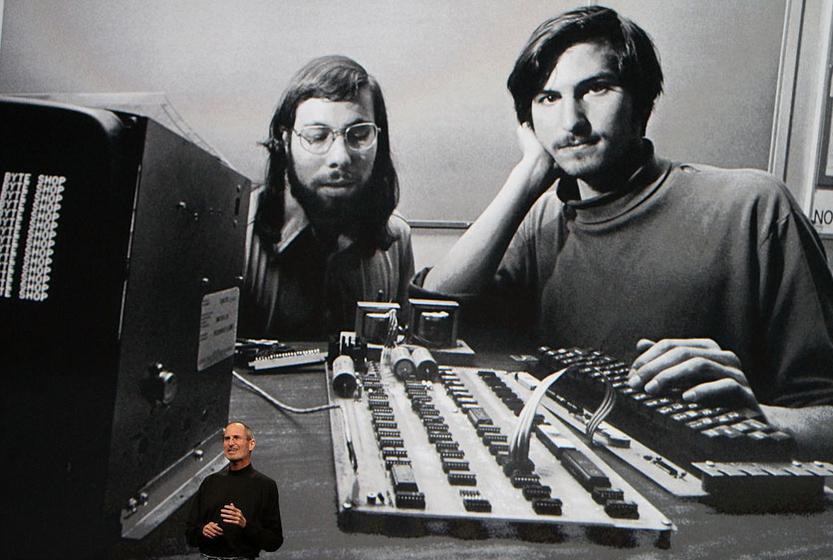 2010年1月27日,苹果公司CEO乔布斯当日在旧金山召开发布会宣布推出平板电脑iPad,他身后的大屏幕显示苹果公司早期,乔布斯(右)和联合创始人沃兹尼艾克。 Justin Sullivan/CFP  _特辑:乔布斯苹果征程