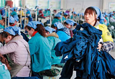 2012年3月23日,安徽淮北市,秋艳服装厂的女工在生产车间内加工出口欧美地区的服装产品。