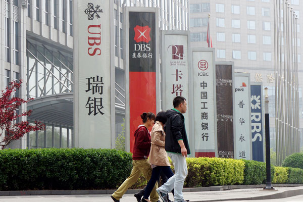 Under relaxed rules, foreign banks will have more access to the yuan-denominated retail banking and bond business. Above: Signs of foreign banks on Financial Street in Beijing. Photo: Visual China