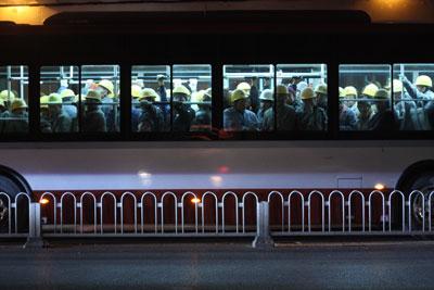 2012年11月28日,下班高峰期间,北京一辆载满农民工的班车行驶在桥下。