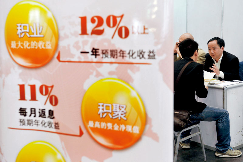 Trillions of yuan have poured into the asset-management business, as retail investors snapped up the short-term, high-yield investment products. Above: A bank employee markets wealth-management products to a client. Photo: Visual China