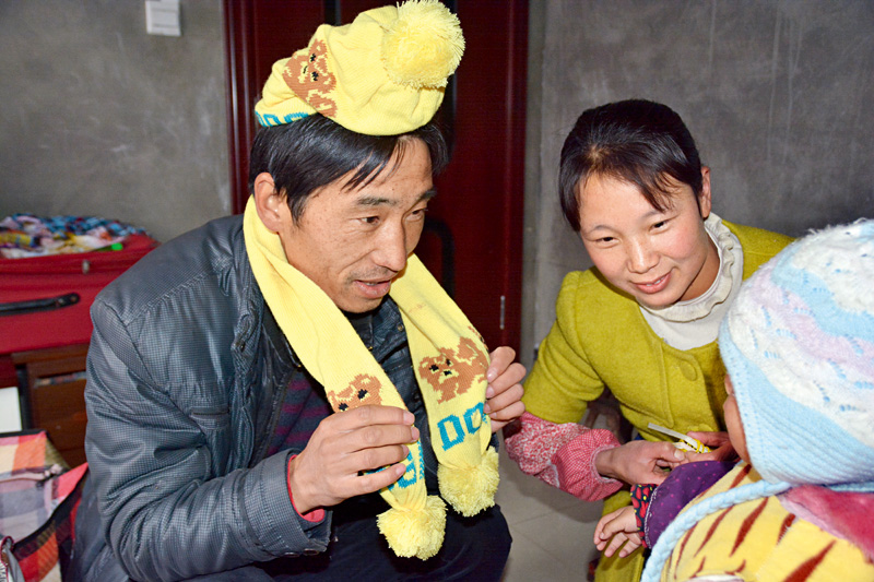 Family planning volunteer Qin Yulu (left) visits a mother and her child in Shanyang County, Shaanxi Province