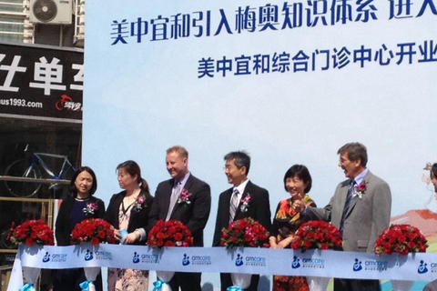 Amcare executives and doctors take part in the ribbon cutting ceremony for a new clinic in Beijing