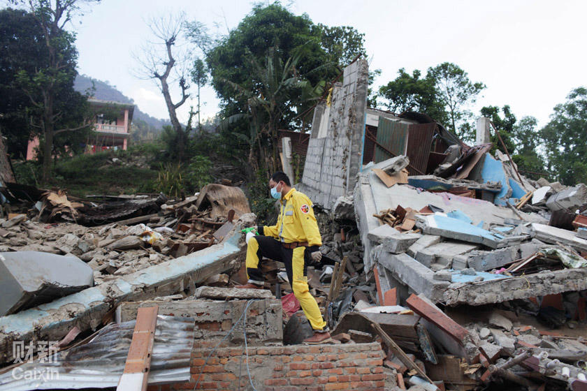 A Chinese volunteer helps clean up a village in Nepal that was badly damaged by the April 25 earthquake