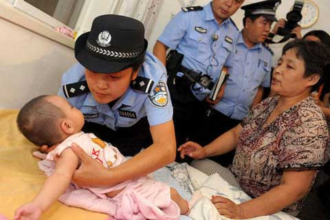 Police rescue a baby girl in Tang County, Hebei Province in a child trafficking crackdown in July in 2012