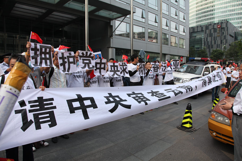 Protestors fearful they have lost investments sold to them by a commodities exchange hold up banners in front of the securities regulator's offices in Beijing on September 21
