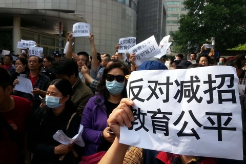 """Parents holding signs that read """"oppose reduced enrollment, education equality"""" protest outside the provincial education department in Nanjing, in the eastern province of Jiangsu, on May 14"""