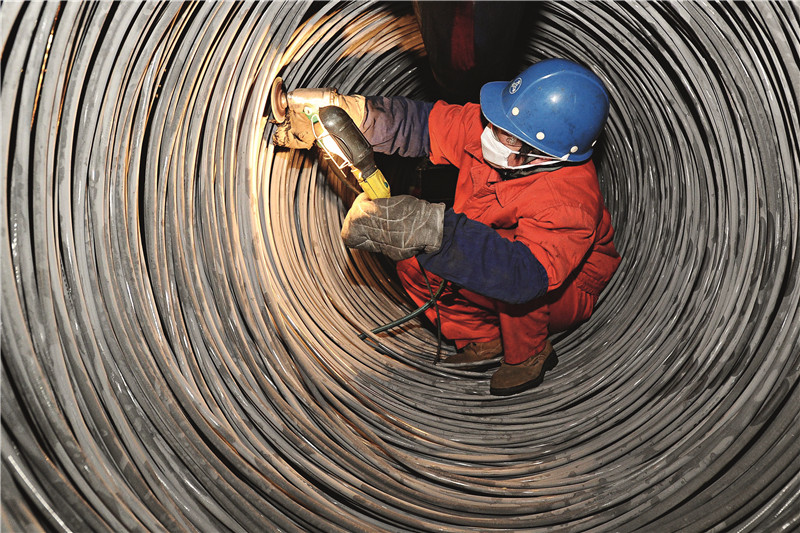 Workers check the quality of steel products at state-owned Dongbei Special Steel Group Co.in the northeastern province of Liaoning. The company defaulted on 700 million yuan worth of debt earlier in May