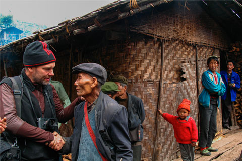 Fritz Hoffmann on assignment for National Geographic magazine being greeted by village party chief on China's border with Myanmar / photo courtesy Fritz Hoffmann