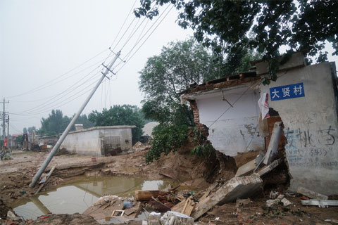 A tilted power line and a damaged home in the city of Xintai, in the northern province of Hebei, where floods killed 34