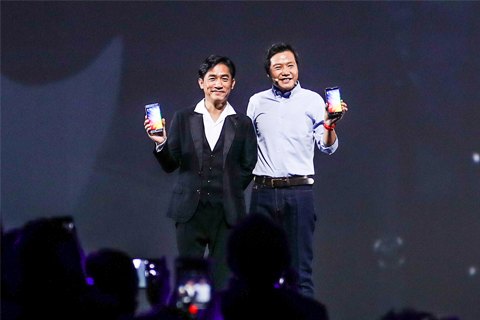 Lei Jun (R), founder and chief executive of Xiaomi Corp., and Hong Kong actor Tony Leung Chiu-wai, pose for pictures at a launch event for the new smartphones Mi Note 2 and Mi MIX in Beijing on Oct. 25. Photo: Visual Chin