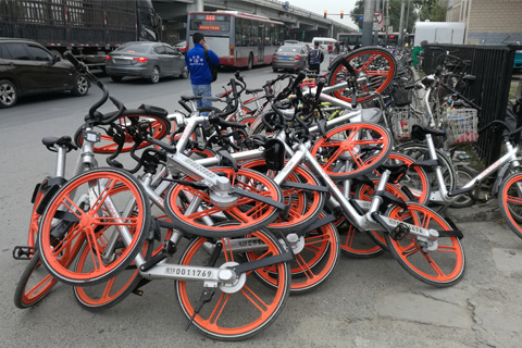 Mobikes left by commuters are piled up near the entrance of a railway station in eastern Beijing on Oct. 27. Photo: Wu Gang