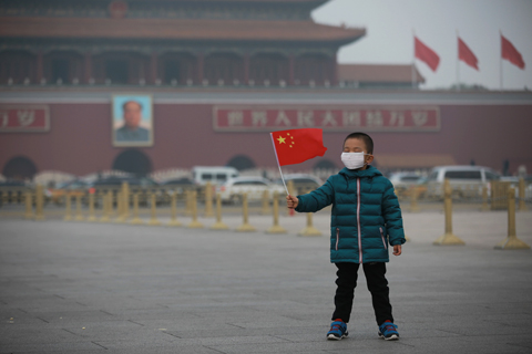 A boy wearing a smog mask waves a Chinese flag at Tiananmen Square on Nov. 10, a day when Beijing was hit by a heavy bout of smog. Photo: IC