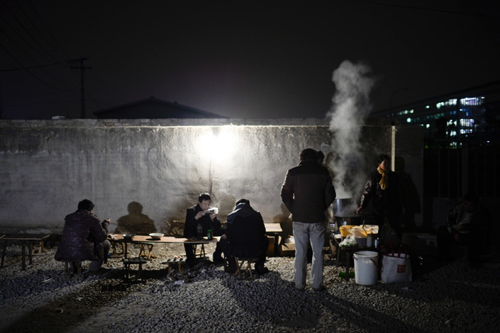 Residents of Houchangcun village, most of whom are Didi drivers, eat dinner in the night market on Nov.13. The village, in Beijing's Zhongguancun district, is surrounded by giant Internet companies, a famous primary school and luxury residential areas. Photo: Yang Yifan/Caixin